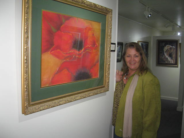 Artist Anita Lee stands beside one of her works.
