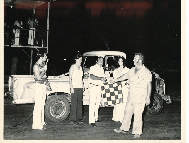 Dale Peters accepts congratulations from promoter Ernie Cook for his 1973 Novice Division championship in Maquoketa, Iowa. Announcer Tom Feller and a trophy girl look on. Photo from Phil Roberts collection.