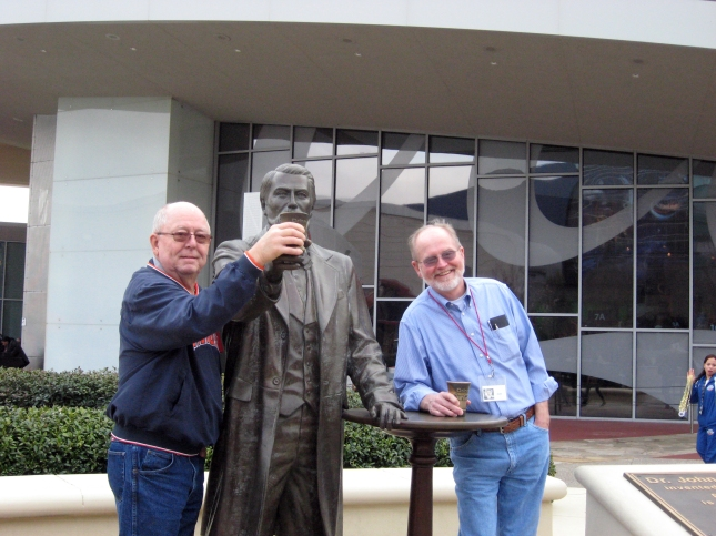 "At the World of Coca-Cola, two fellow passengers ""enjoy a Coke"" with its inventor, John Pemberton."
